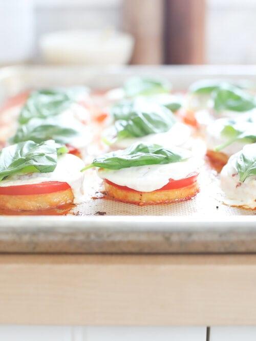 Baked polenta margherita pizzas on a baking sheet.