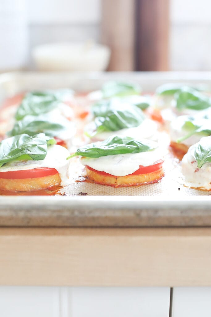 Baked polenta margherita pizzas on a baking sheet.