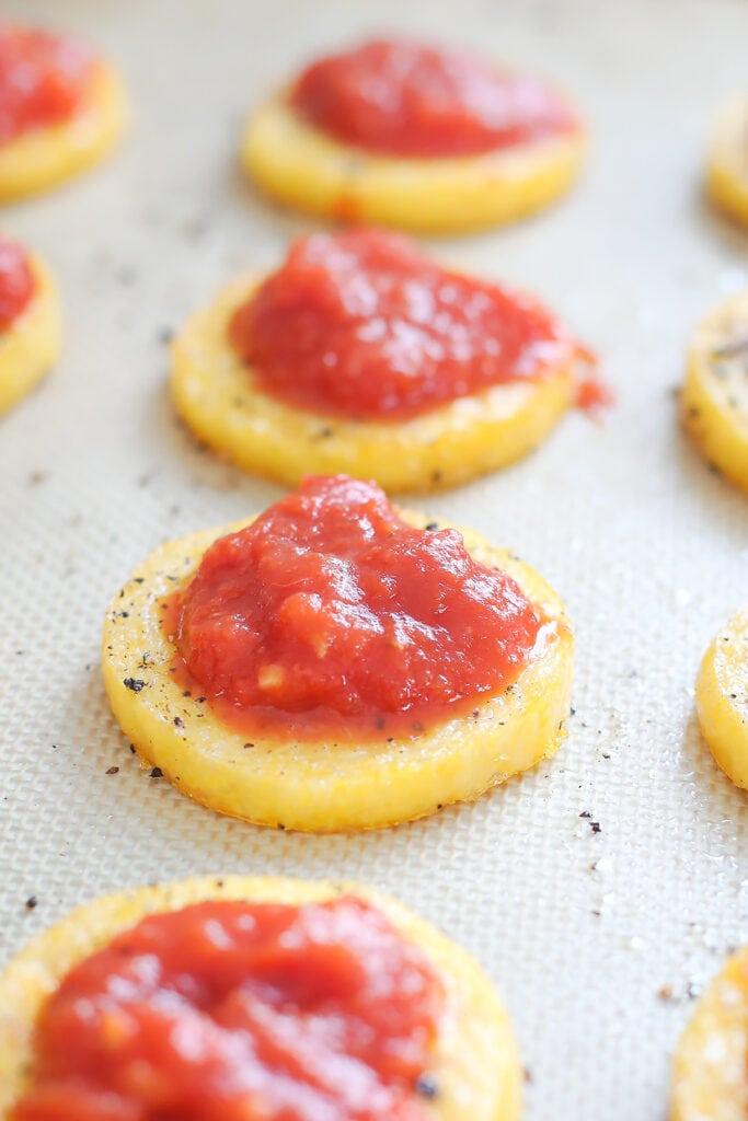Baked polenta margherita pizzas being made on a baking sheet.