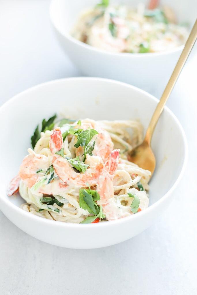 Dairy-free, vegan shrimp fettuccine alfredo in a white bowl.