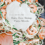 Dairy-free alfredo sauce over shrimp and noodles in a cast-iron pan.