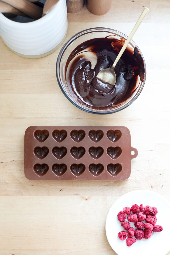 Silicone heart mold being filled with raspberries and easy homemade chocolate.
