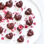 Easy homemade raspberry chocolates on white plate.