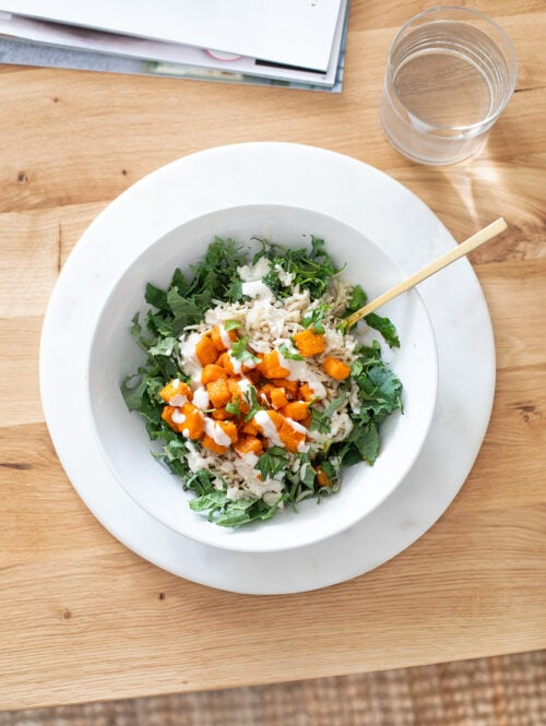 Baked buffalo tofu with kale and brown rice in a white bowl on a table.
