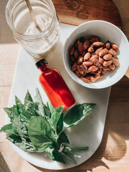 Grain bowl toppings (basil, almonds, hot sauce, and tahini sauce) on a counter.