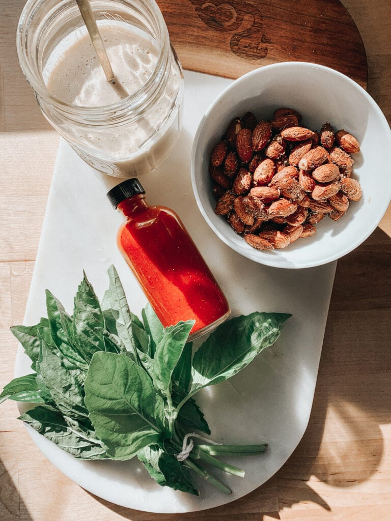 Grain bowl toppings (basil, almonds, hot sauce, and tahini sauce) on a counter.