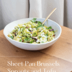 Miso maple sheet pan brussels sprouts and tofu in a white bowl on a wooden table.