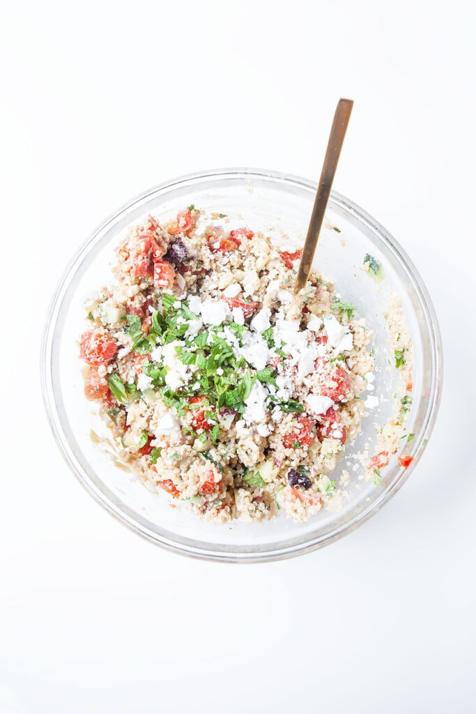 Greek quinoa salad in a glass bowl on a white table.