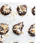 Frozen chocolate banana bites on a sheet pan with parchment paper.