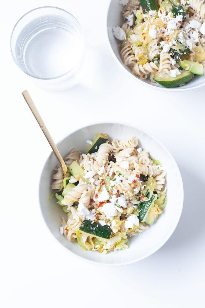 Lemony zucchini pasta in a white bowl.