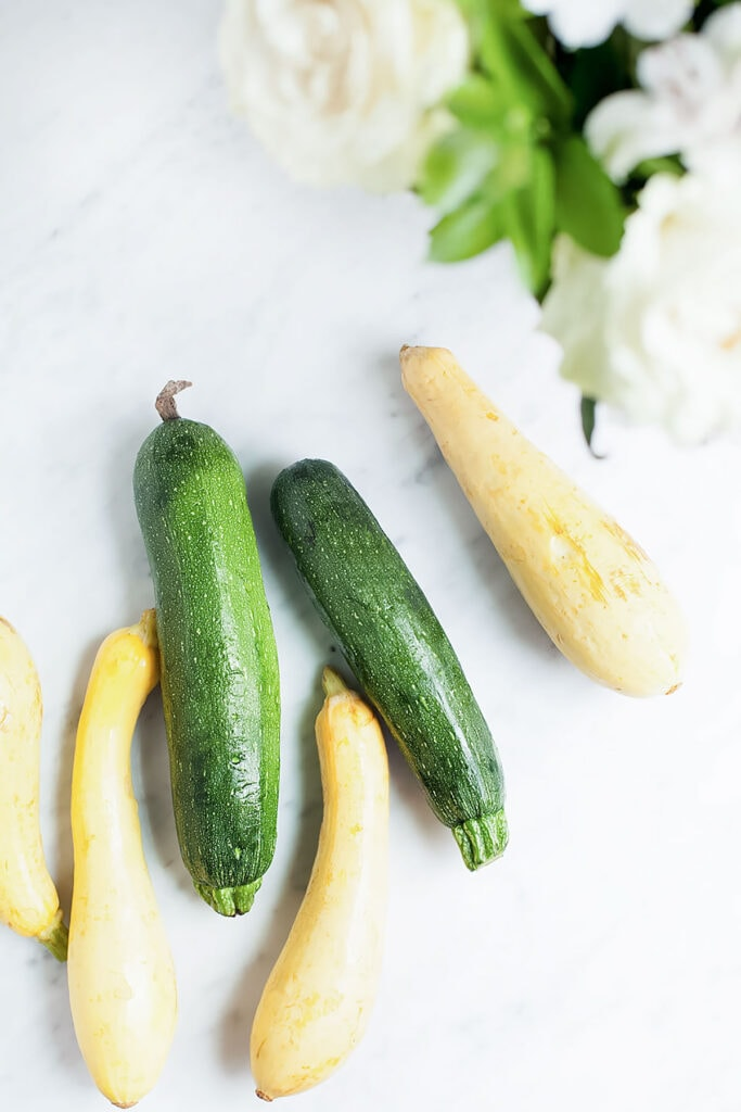 Zucchini on a white marble counter.