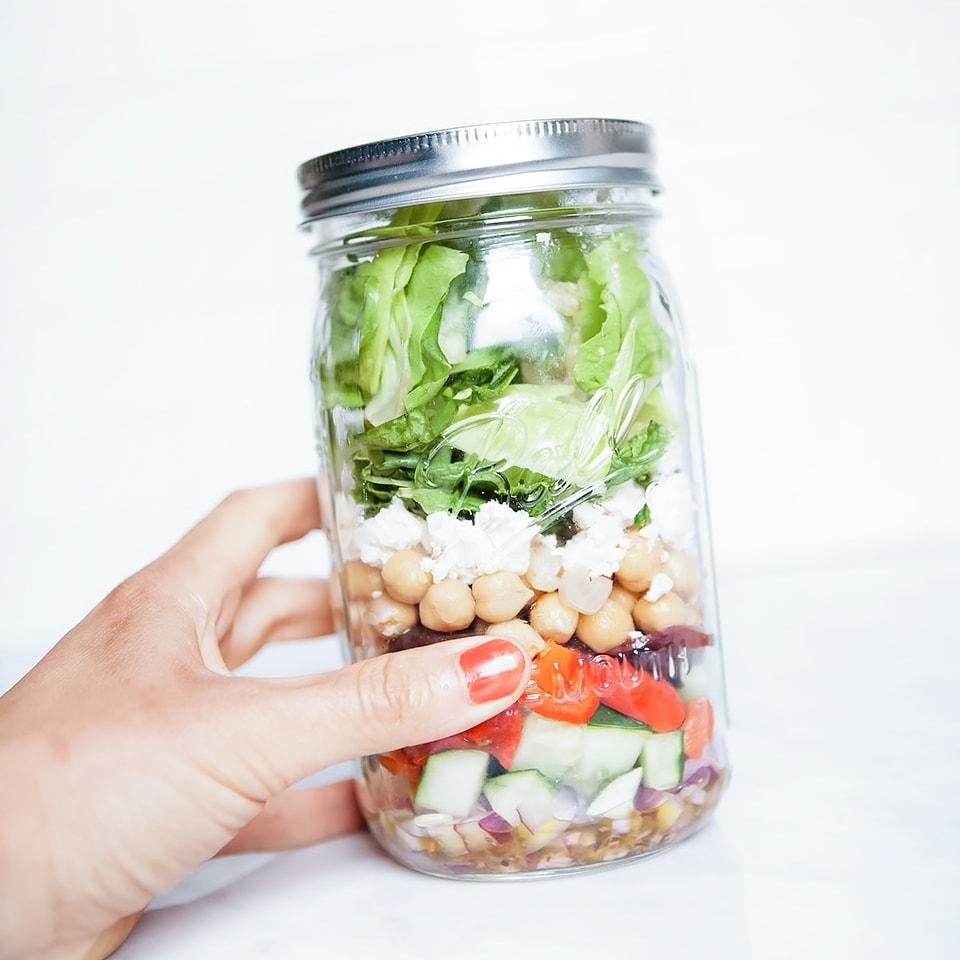 Greek chopped salad being held in a mason jar.