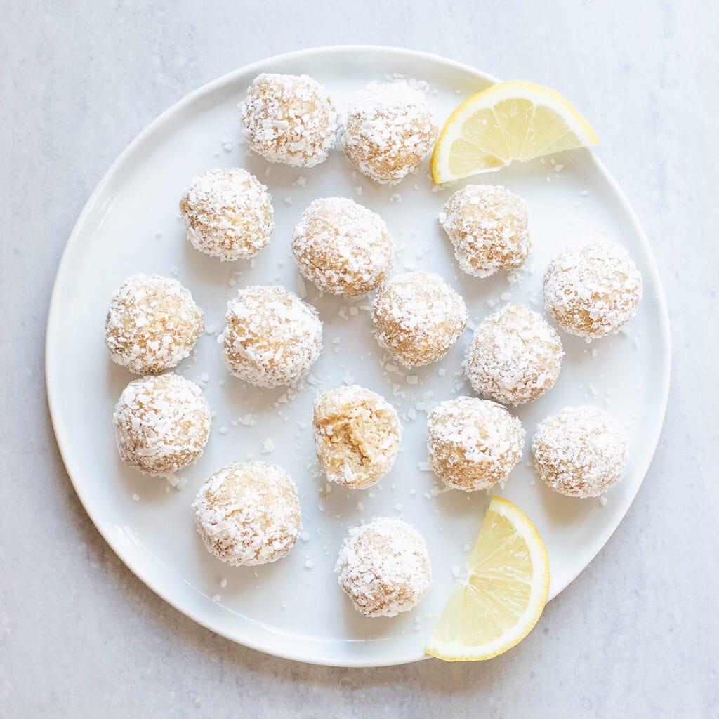 Lemon coconut energy bites on a white plate.