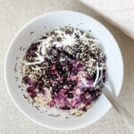 Overnight oats with blueberries and coconut in a white bowl with fabric background.