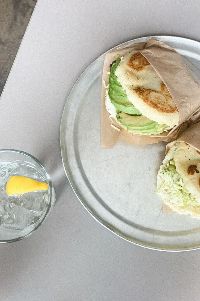 Avocado arepas and a glass of lemon water.