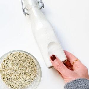 Homemade hemp milk and hemp seeds on a white countertop.