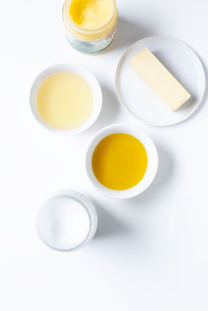 Healthy fats and oils for cooking on a white background.