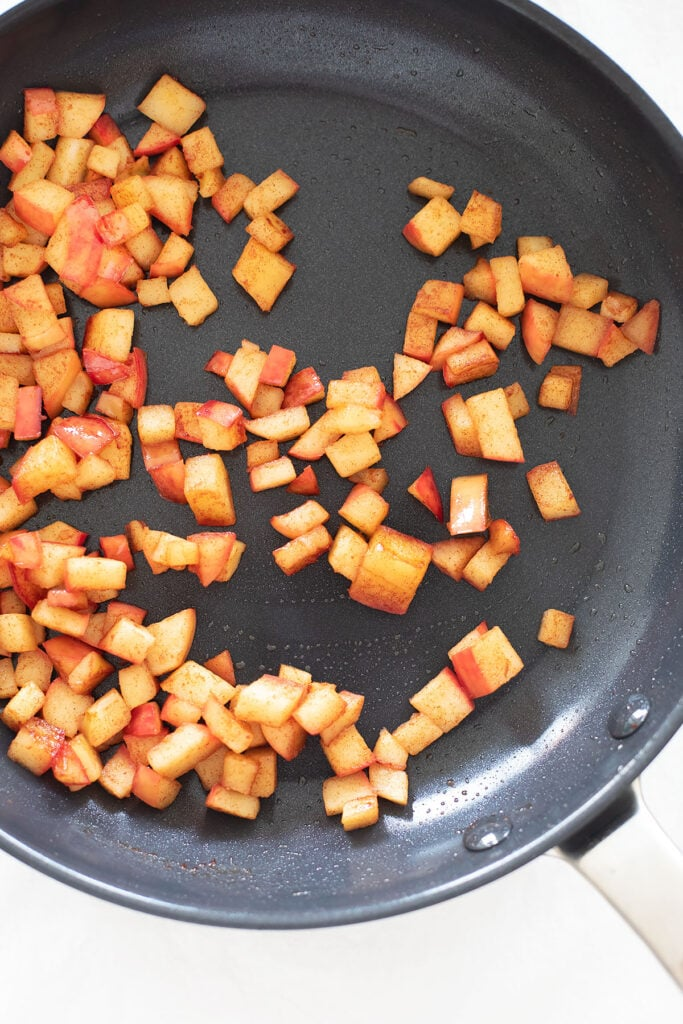 Diced apples being sautéed in a frying pan.