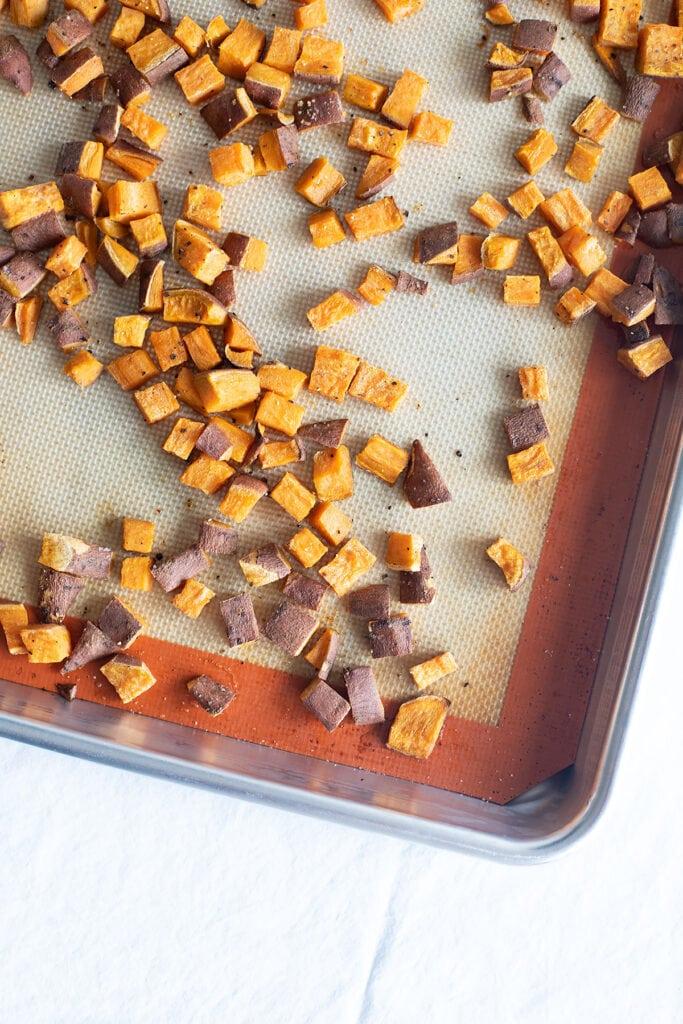 Roasted sweet potato cubes on a sheet pan.