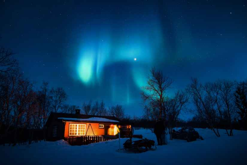 brown cottage under aurora borealis