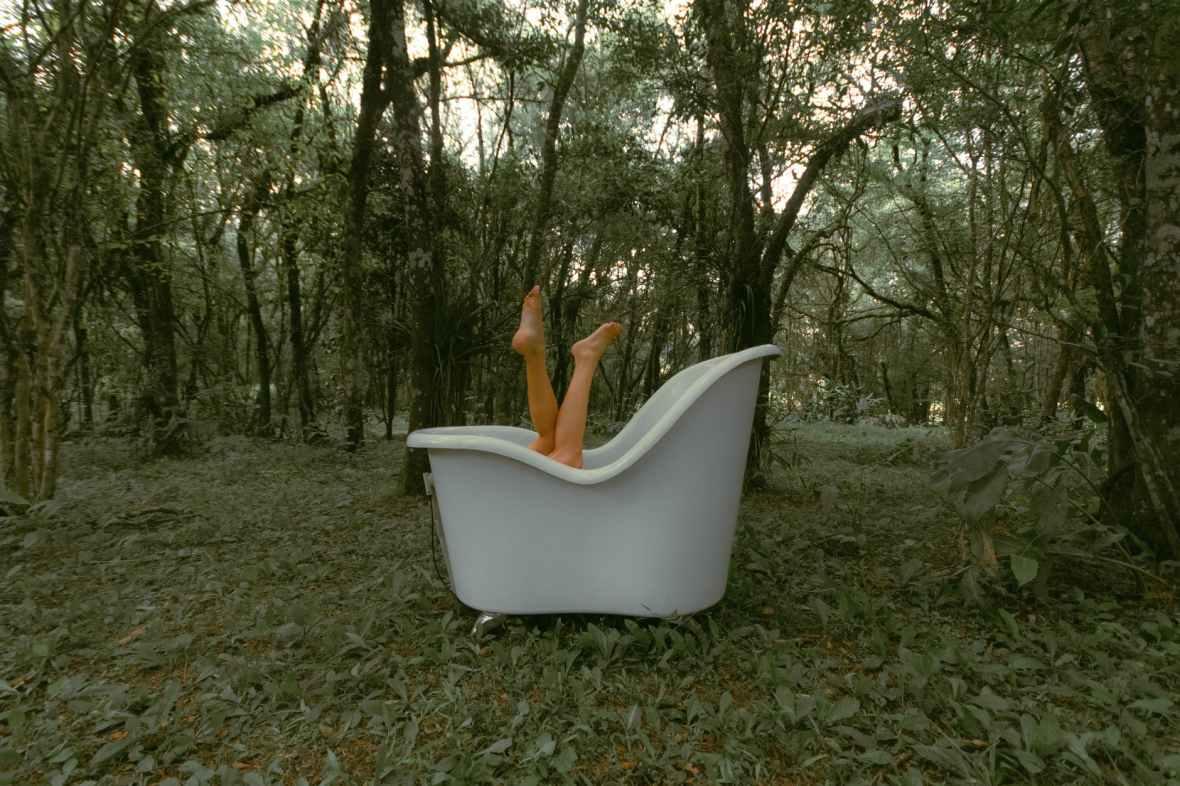 crop woman in bath in forest