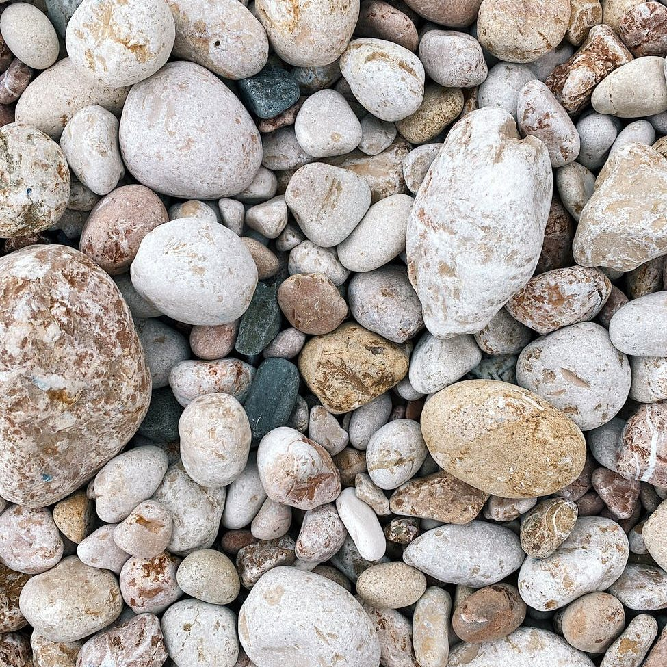 different pebbles on beach as abstract background