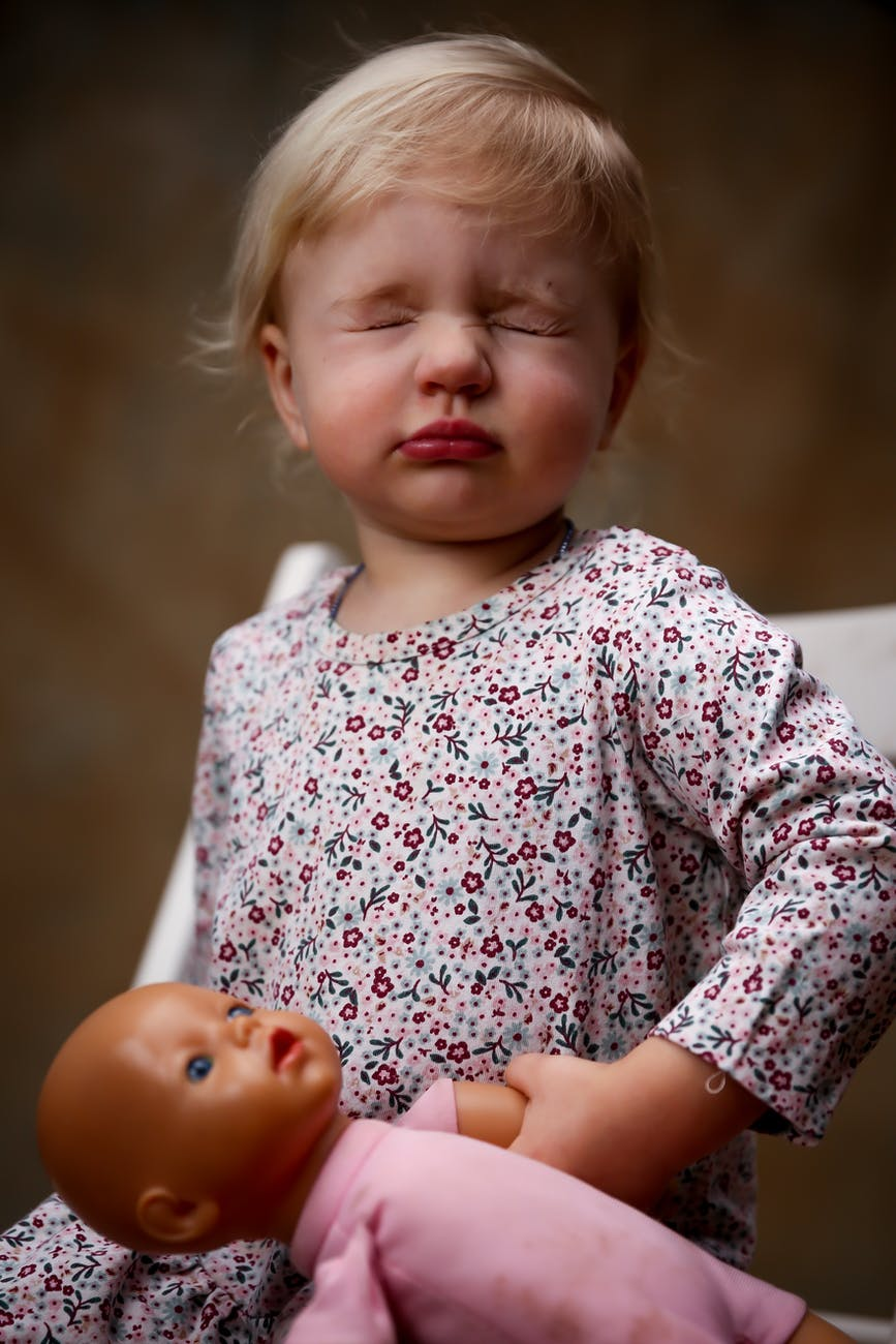 toddler wearing floral dress holding doll