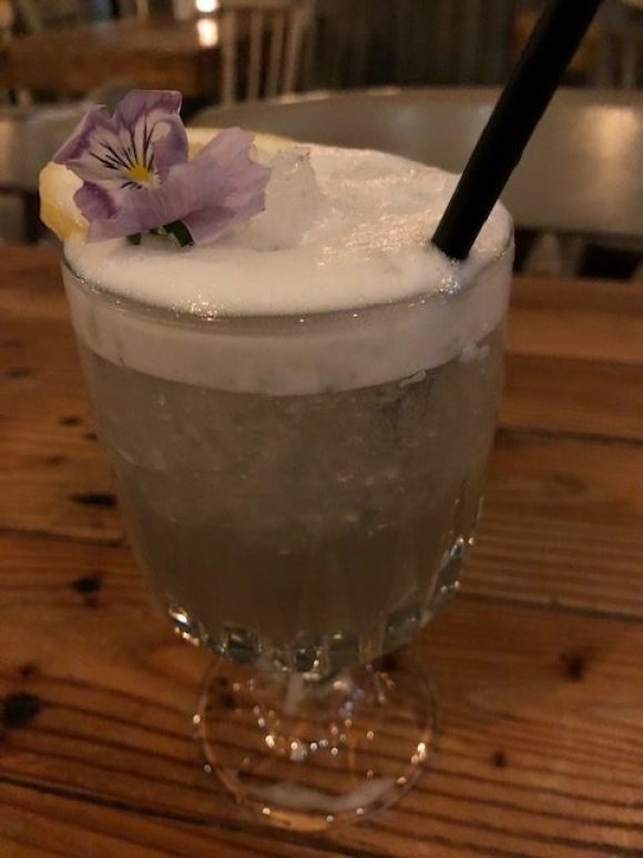 cocktail bars in Derbyshire - a violet cocktail decorated with edible flower
