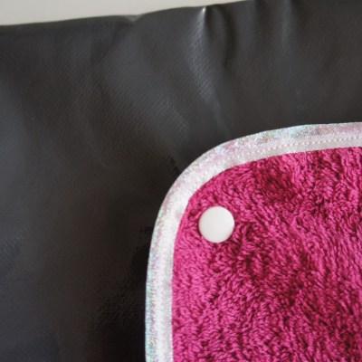 Zoom sur le tissu enduit et la serviette éponge bordée de biais blanc transparent irisé / pailleté.