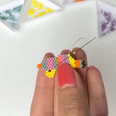 Augmentation en fin de rang brick stitch : Enfilez la dernière perle et passez sous le fil qui joint la perle du rang précédent et la perle par laquelle sort le fil actuel.