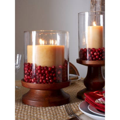 Use cranberries to decorate a hurricane candle holder