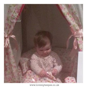 little girl opening her present inside the pink rose teepee