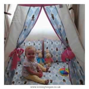 child sat on a floor mat inside peter rabbit radishes teepee edged in pink