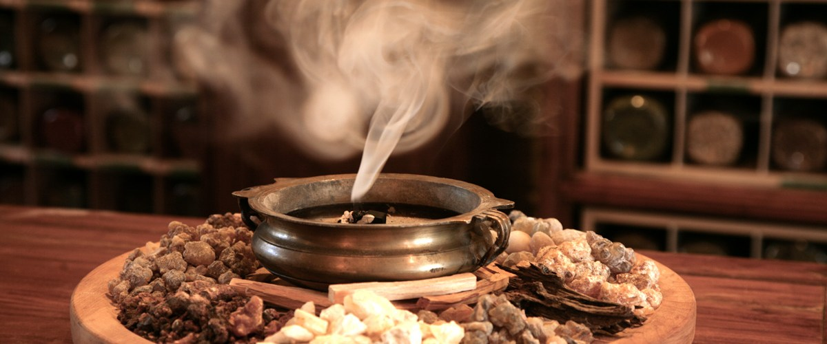 Frankincense, myrrh, and other resins burning in an antique brass pot.