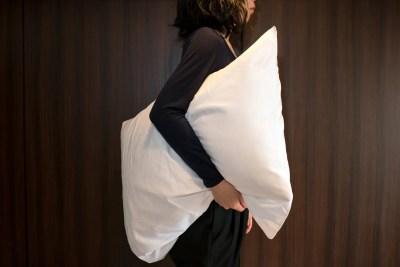 枕を持つ女性 寝床を変える妻