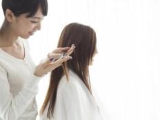 縮毛矯正のために髪質をチェックする美容師