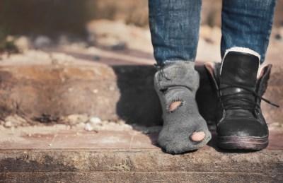 敗れたソックスと汚い靴