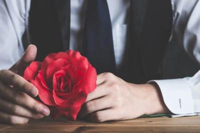 女性をデートに誘おうとしているバラを持つ男性