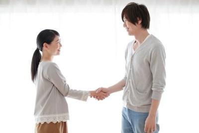 握手をして挨拶をする夫婦