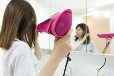 ドライヤーで髪を乾かす女性