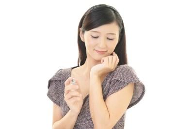 香水瓶を持つ女性