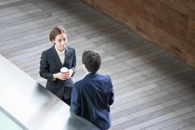 屋外でコーヒーを飲みながら仕事の相談をする男女
