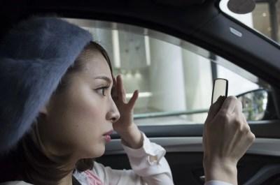 女性は車内でメイク直しをしている