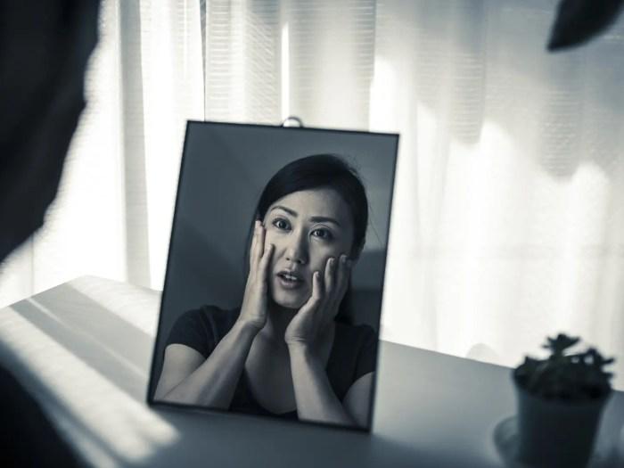 鏡をみている痛い女性