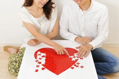 仲良く赤いハートのパズルゲームをしている日本人カップル