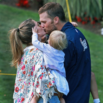08/11/14: Foxborough, MA: As he left the field following practice, Patriots quarterback Tom Brady was met by his wife Gisele Bundchen and they shared a kiss as their daughter looked on. Brady was holding his son who is behind them. The New England Patriots held an afternoon practice session on the fields outside of Gillette Stadium. (Globe Staff Photo/Jim Davis) section:sports topic:Pats practice