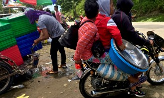 overloaded motorcycle trasnports a stall holder home from a religous festival in rural Philippines