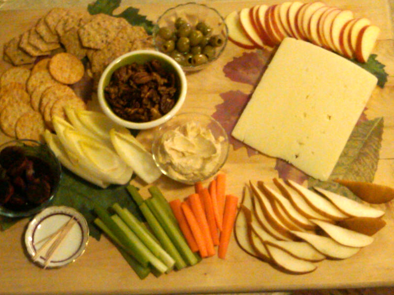Cheese, crackers, and vegetables appetizer on a wooden serving board.