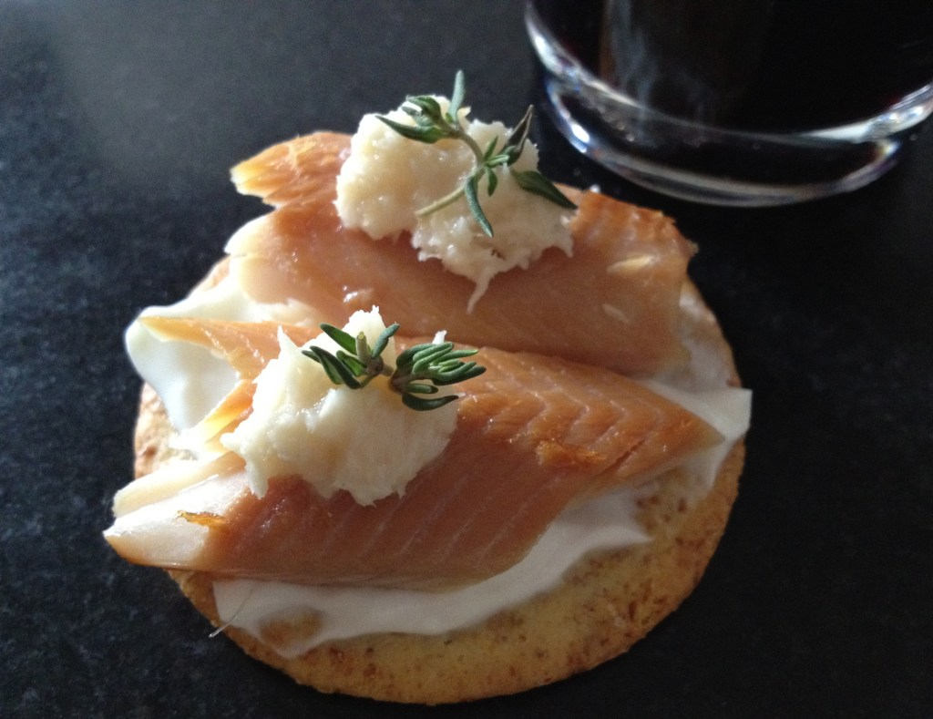Smoked trout on a  cracker with plain Greek yogurt and horseradish.