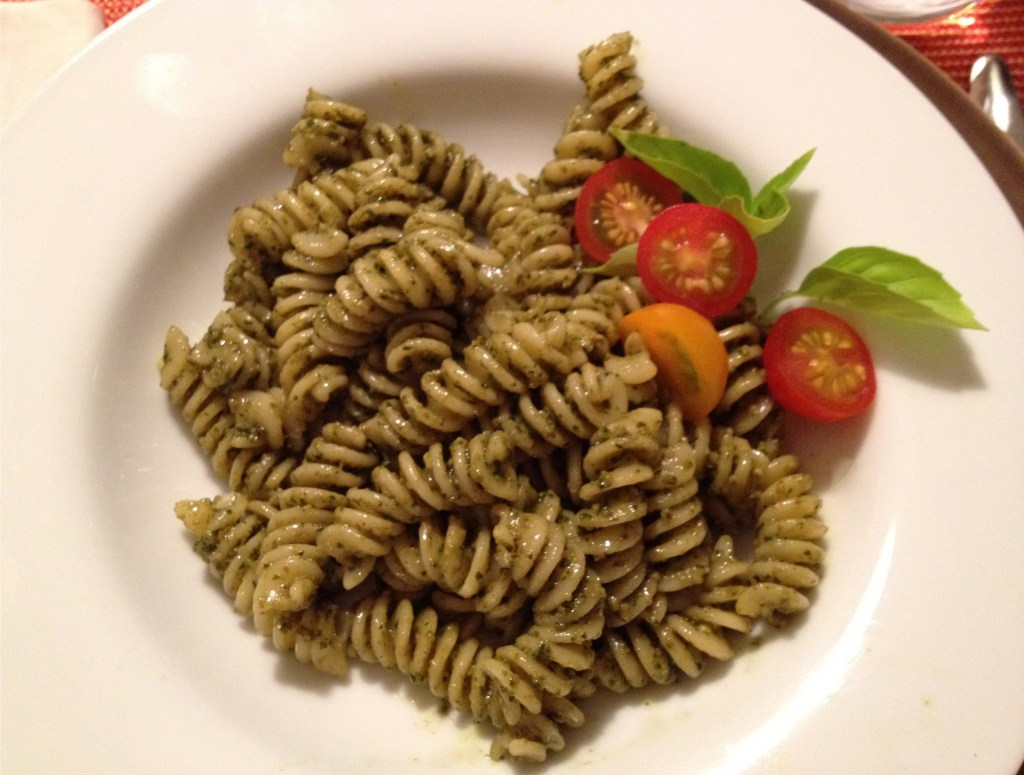 Pesto pasta and tomatoes in a white bowl.